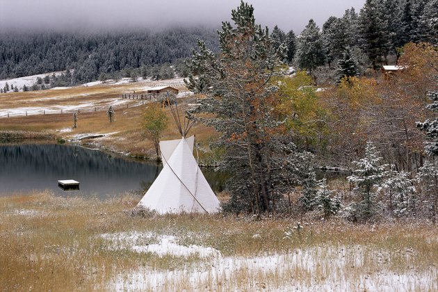 A view of an Indian teepee, patches of snow cover the ground