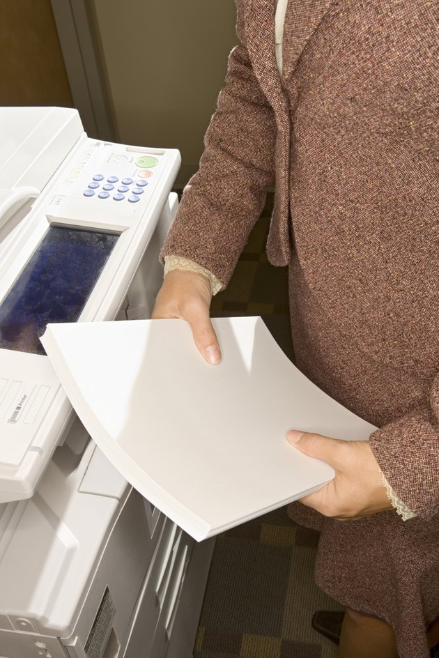 Woman holding paper next to copy machine