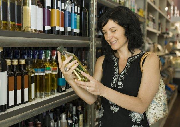 Customer holding bottle of oil in grocery store