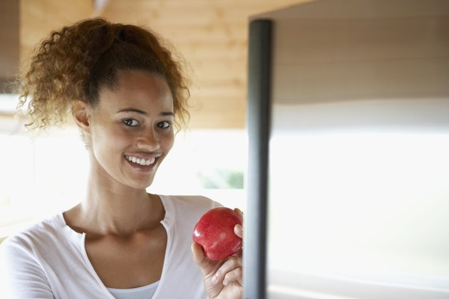 Mixed Race woman holding apple