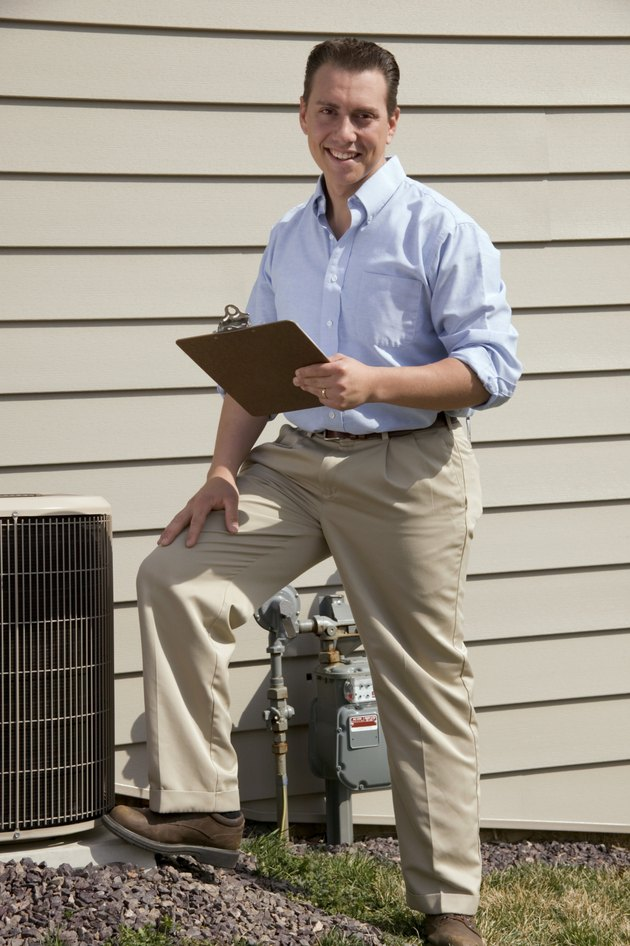 Man with clipboard standing near air conditioning unit