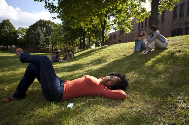 student laying on grass