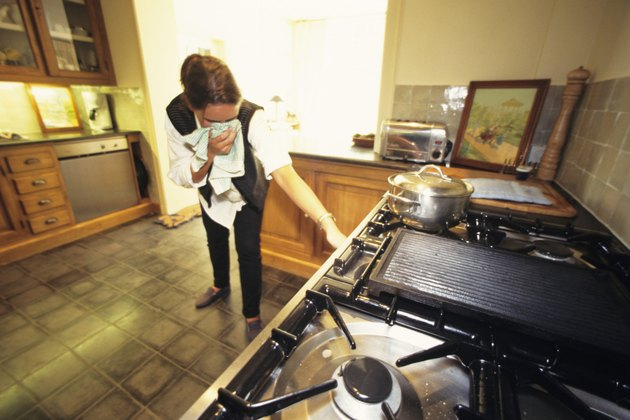 Woman in kitchen, turning off gas cooker, towel to face