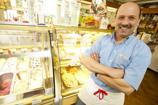 Store manager standing in front of gelato freezer
