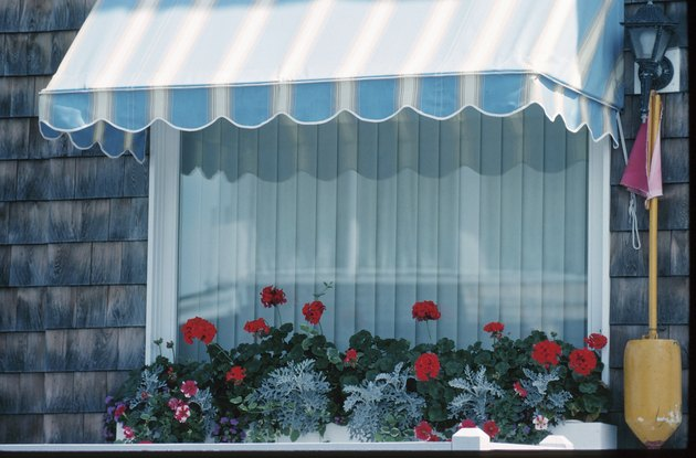 Close-up of a window with geraniums and a stripy awning