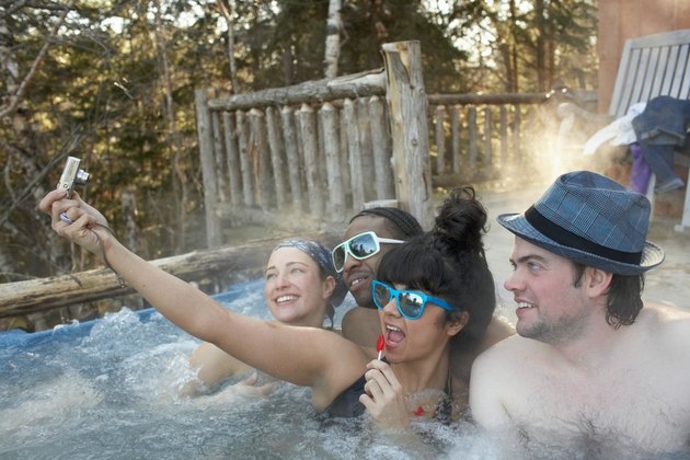 Young people frolicking in hot tub, taking digital self portrait