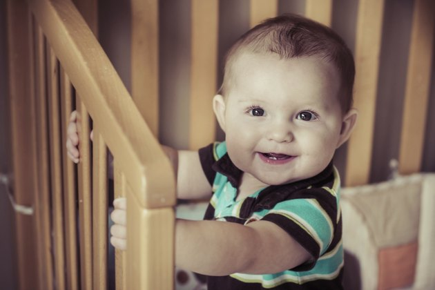 Happy baby standing up in his crib