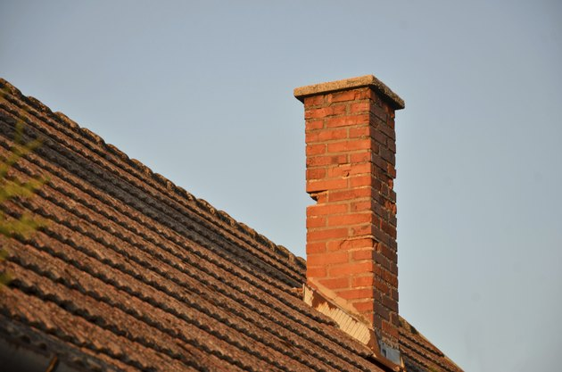 Orange roof tiles, brick chimney and blue sky