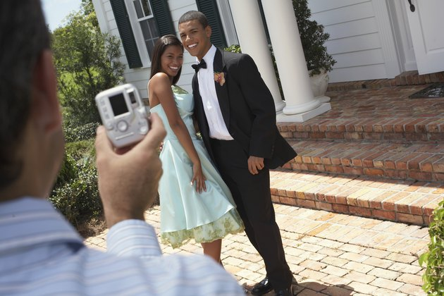 Man photographing young couple wearing evening dress, outdoors,smiling