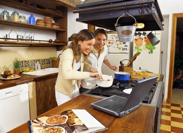 Couple cooking while using a laptop
