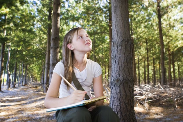 Girl writing in notebook in forest