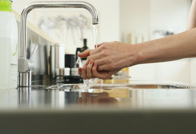Woman washing hands at kitchen sink, view along counter, close-up