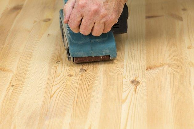 Mans hand on belt sander with pine wood