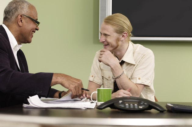 Mature man laughing with young man in the office