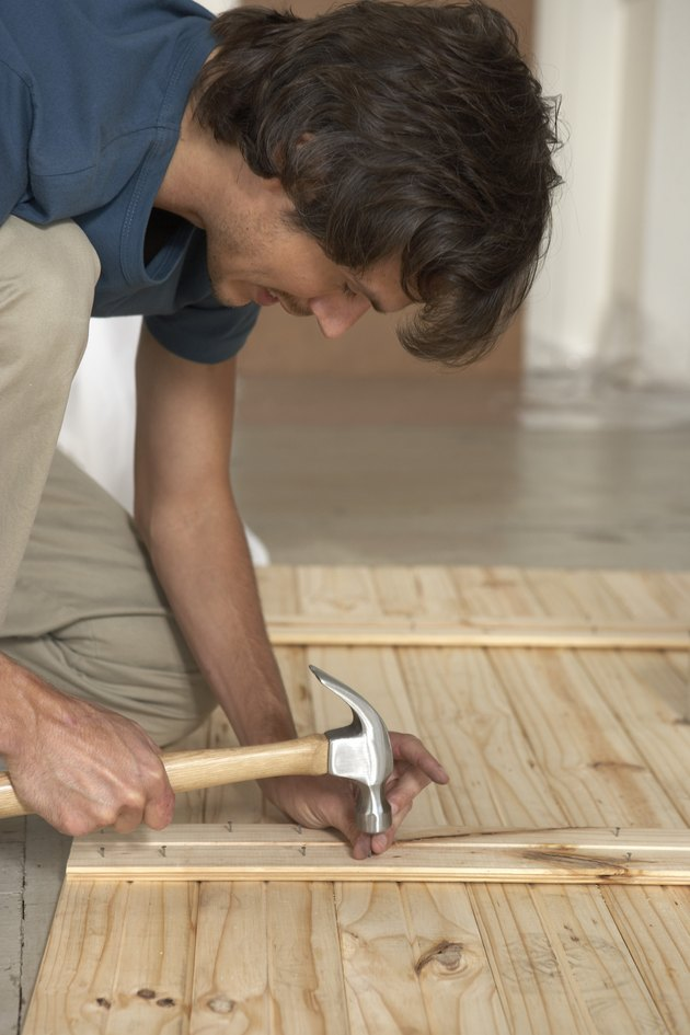 Man hammering nail into lumber