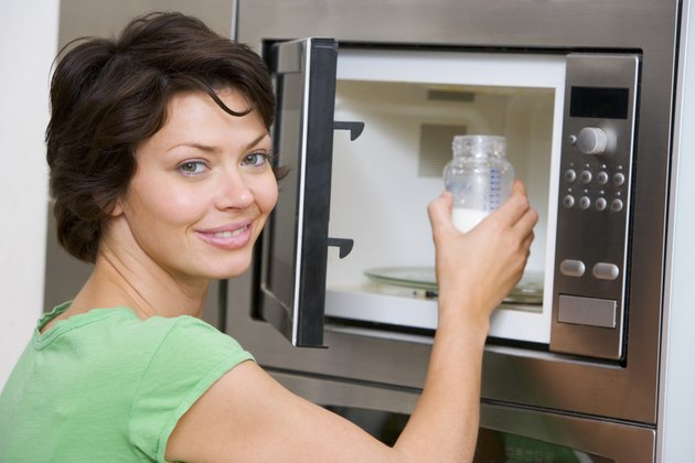 Woman microwaving bottle