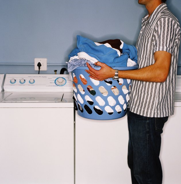 side profile of a man holding a laundry bin full of clothes
