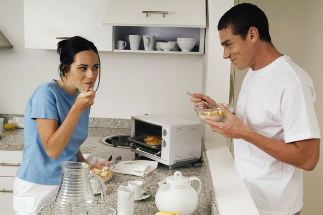 Young couple standing in kitchen having breakfast