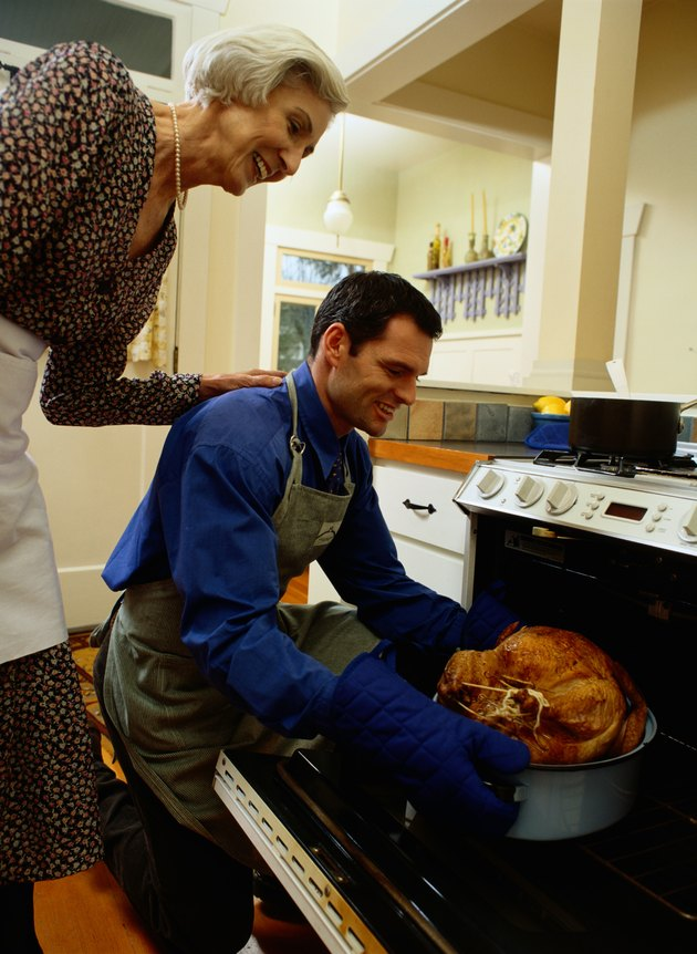 Man and Woman Putting a Turkey in the Stove