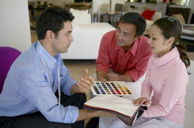 Couple Discuss Fabric Swatches and Colour Charts With an Assistant in an Interiors Shop