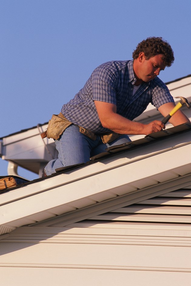 Man putting shingles on roof