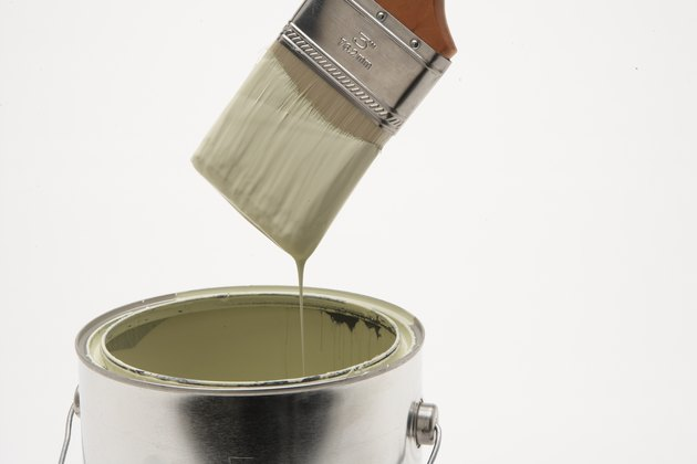 Paint running off paintbrush into paint can