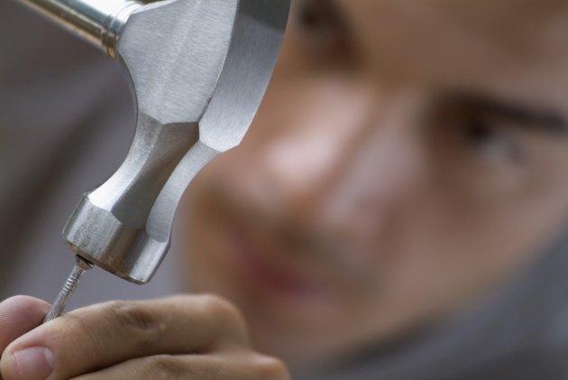 Man hammering nail, focus on hammer and nail, close-up