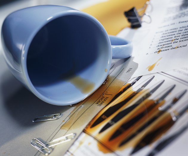 Overturned coffee cup; coffee spilled over papers and file folder