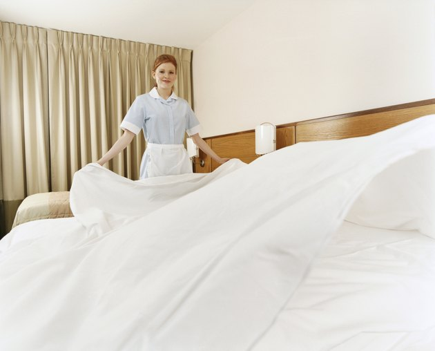 Female Maid Makes a Bed in a Hotel Room