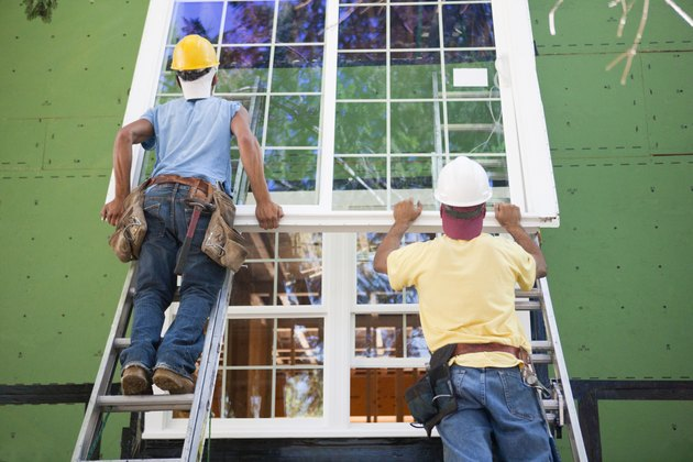 Carpenters positioning a large window frame on a house under construction