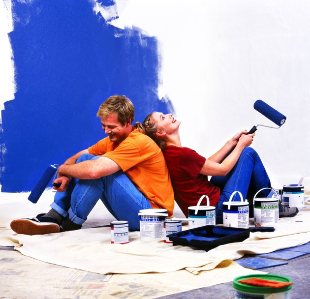side profile of a couple sitting back to back with roller brushes of paint in hand