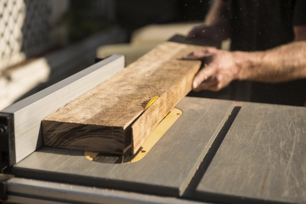 man cutting a thin strip of wood on a table saw