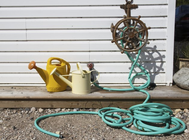 Green water hose and two watering cans outdoors