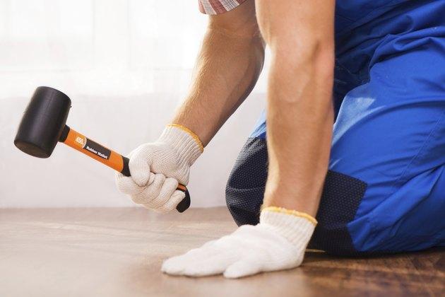 Close-up photo of repairman hammering fabricated wood block flooring