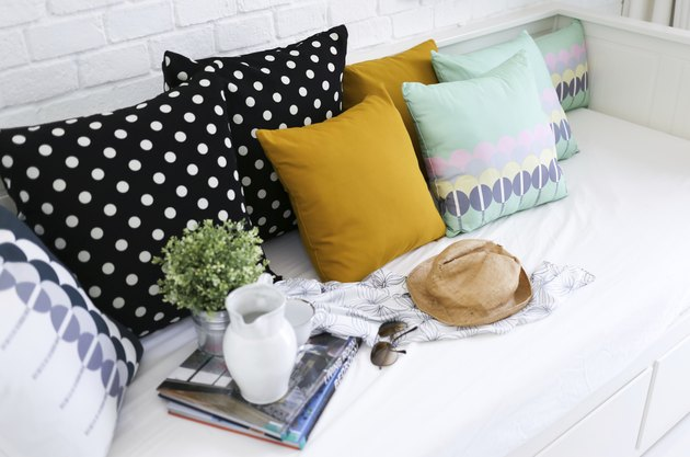 Colorful pillows on a sofa with white brick wall background
