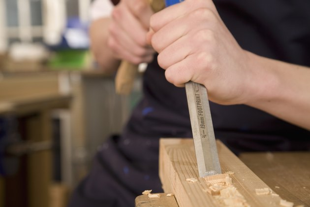 Person carving into wood with a chisel