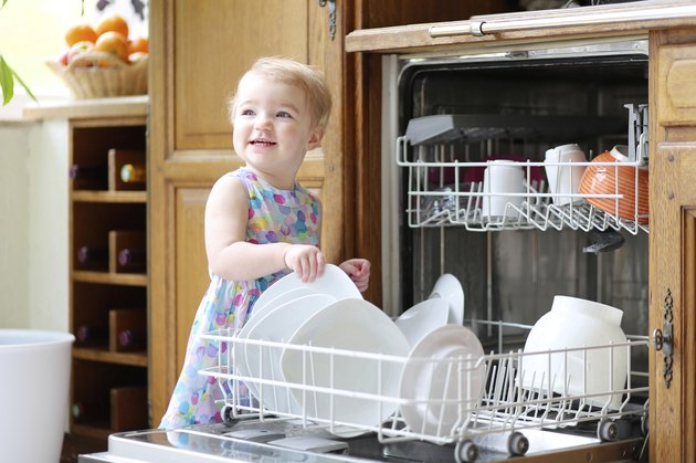 Toddler girl helps in the kitchen with dishes