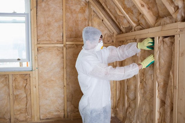 Builder filling walls with insulation
