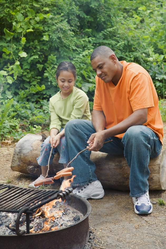 Father and daughter roasting hot dogs in camp fire