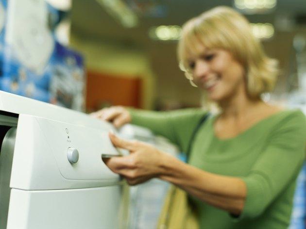Woman in electrical shop opening washing machine
