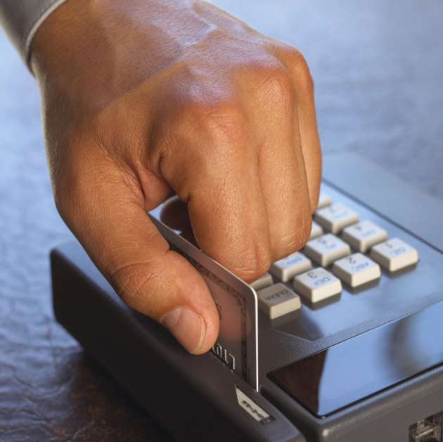 Man sliding credit card through machine