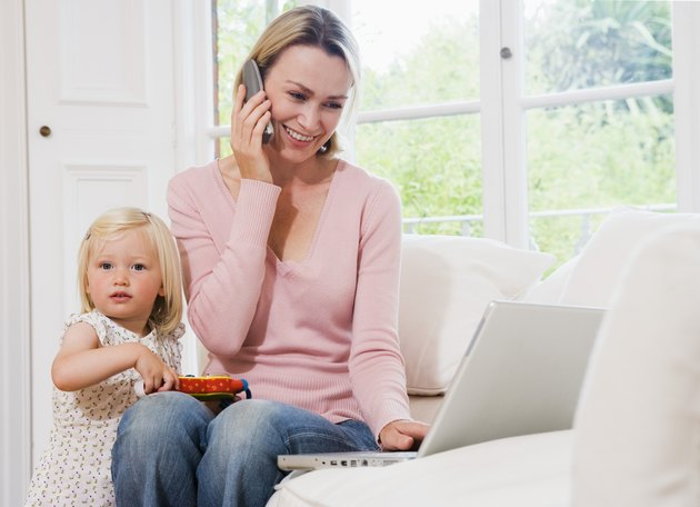 Child playing by mother talking on phone and working on computer