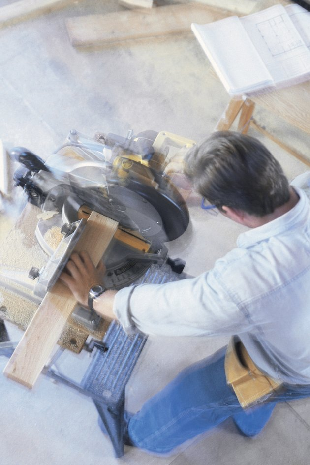Construction worker using a miter saw