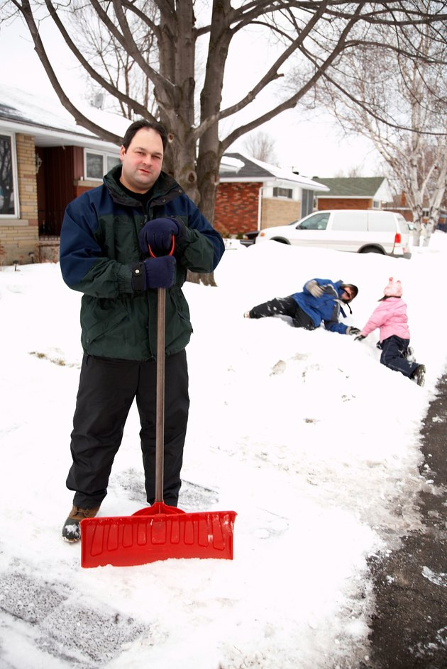 Father posing with snow shovel while children play