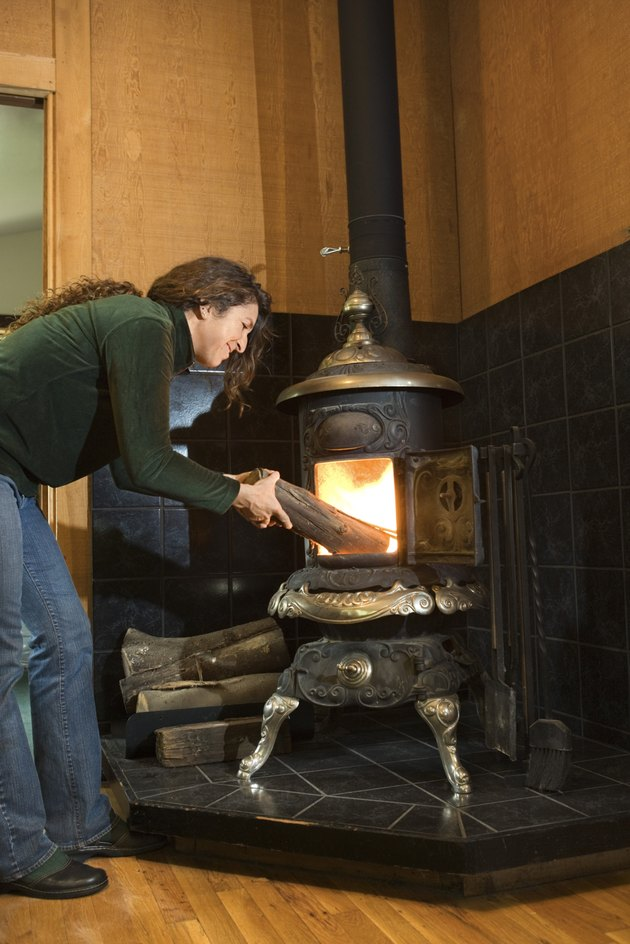 Woman putting firewood into wood stove