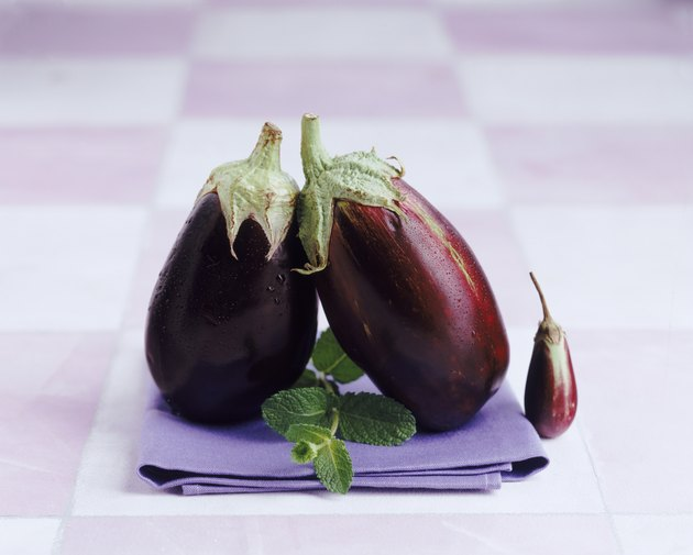 Eggplant with mint leaf on napkin, close-up
