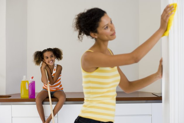 Woman cleaning with girl looking on