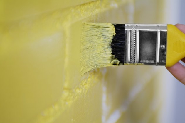 Person painting the wall yellow