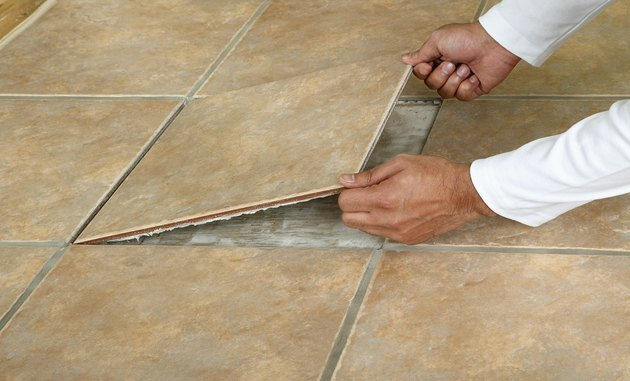 Man removing marble floor tile, close-up