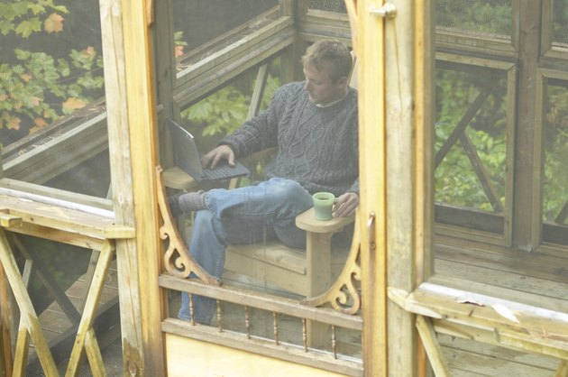 Man relaxing on porch with laptop computer